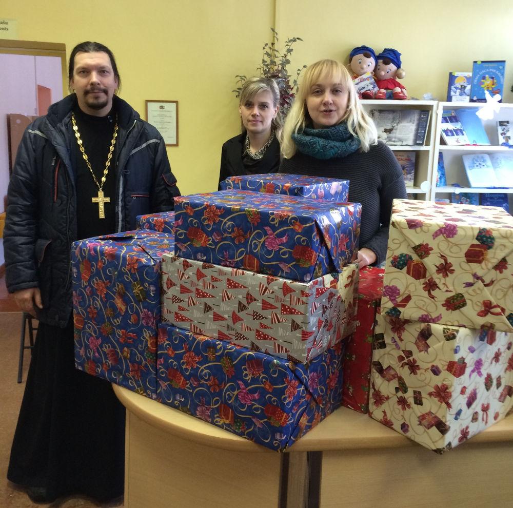 Прот. Виктор Теплов вручает подарок Резекненской детской библиотеке